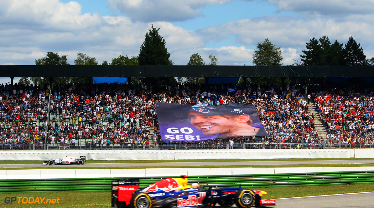 141017788KR00019_F1_Grand_P HOCKENHEIM, GERMANY - JULY 22:  Fans unfurl a giant banner in support of Sebastian Vettel of Germany and Red Bull Racing as he drives by during the German Grand Prix at Hockenheimring on July 22, 2012 in Hockenheim, Germany.  (Photo by Ker Robertson/Getty Images) *** Local Caption *** Sebastian Vettel F1 Grand Prix of Germany - Race Ker Robertson Hockenheim Germany  Formula One Racing
