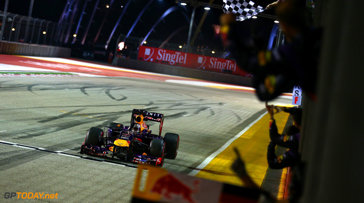 SINGAPORE - SEPTEMBER 22:  Sebastian Vettel of Germany and Infiniti Red Bull takes the chequered flag and victory during the Singapore Formula One Grand Prix at Marina Bay Street Circuit on September 22, 2013 in Singapore, Singapore.  (Photo by Paul Gilham/Getty Images) *** Local Caption *** Sebastian Vettel F1 Grand Prix of Singapore Paul Gilham Singapore Singapore