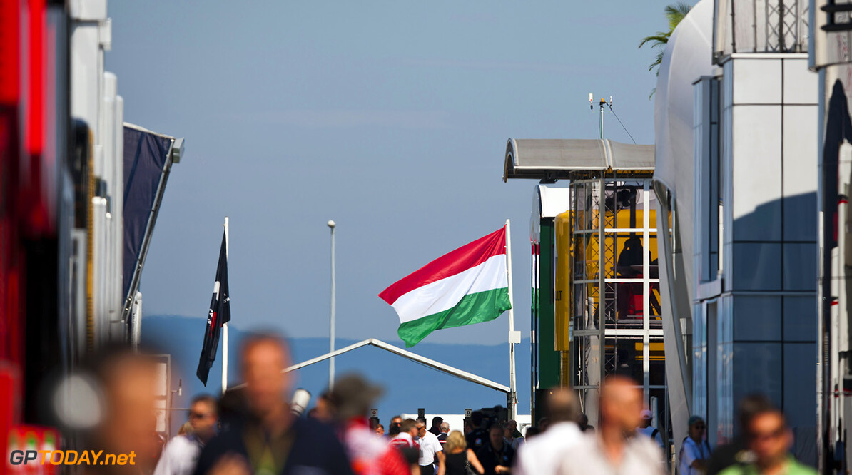 BUDAPEST, HUNGARY - JULY 25:  A Hungarian national flag flaps in the wind as people walk through the paddock during practice ahead of the Hungarian Formula One Grand Prix at Hungaroring on July 25, 2014 in Budapest, Hungary.  (Photo by Drew Gibson/Getty Images) F1 Grand Prix of Hungary - Practice Drew Gibson Budapest Hungary  Formula One Racing formula 1 Auto Racing Formula One Grand Prix