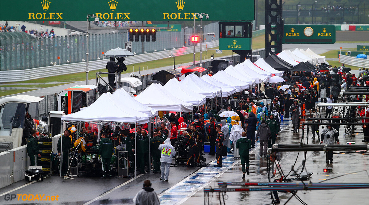 SUZUKA, JAPAN - OCTOBER 05:  Drivers and teams shelter from the rain under awnings in the pit lane as they wait for the race to resume during the Japanese Formula One Grand Prix at Suzuka Circuit on October 5, 2014 in Suzuka, Japan.  (Photo by Clive Rose/Getty Images) F1 Grand Prix of Japan Clive Rose Suzuka Japan  Formula One Racing