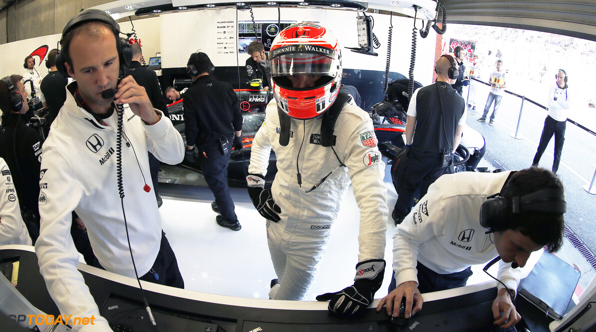Jenson Button with the engineers in the garage.