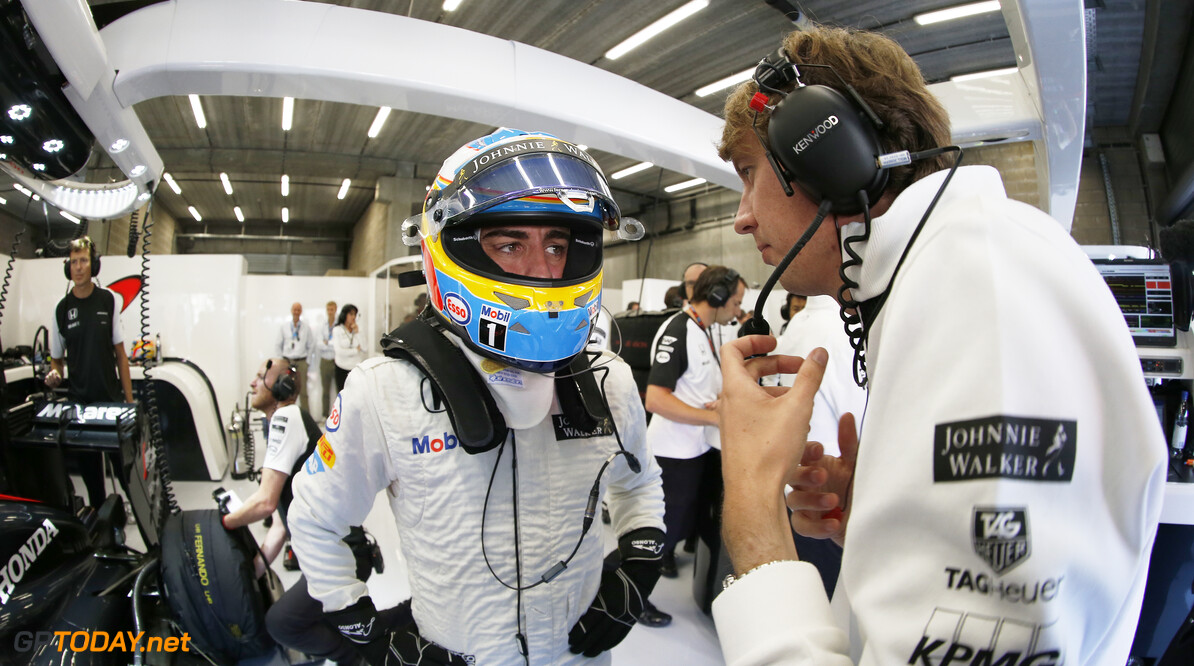 Fernando Alonso talks to an engineer in the garage.