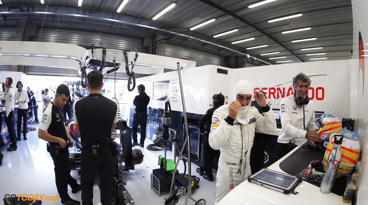 Fernando Alonso puts on his helmet in the garage.