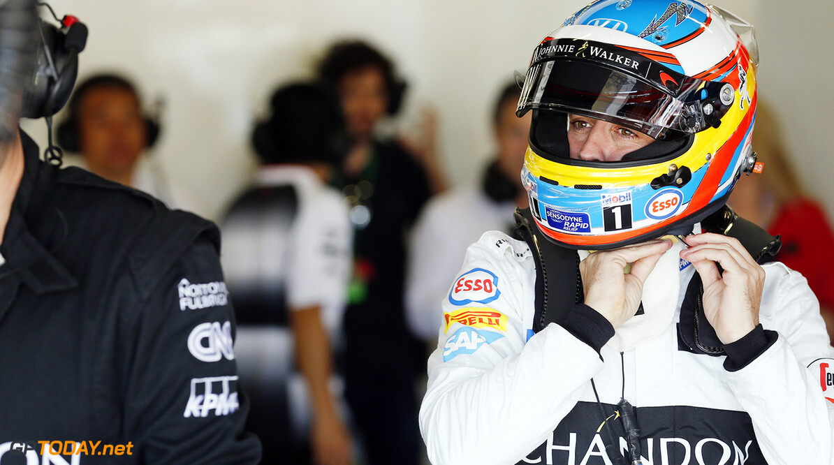 Fernando Alonso adjusts his helmet in the garage.