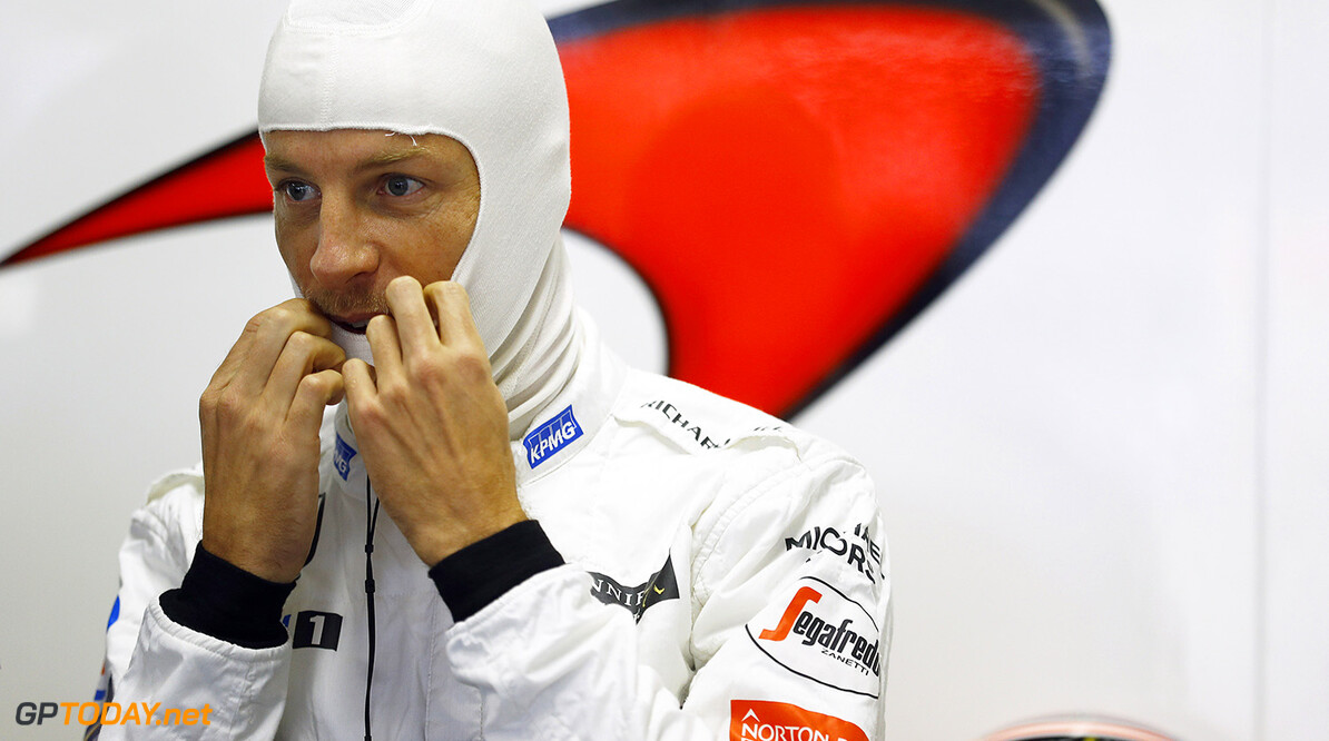 Jenson Button puts on his balaclava in the garage.