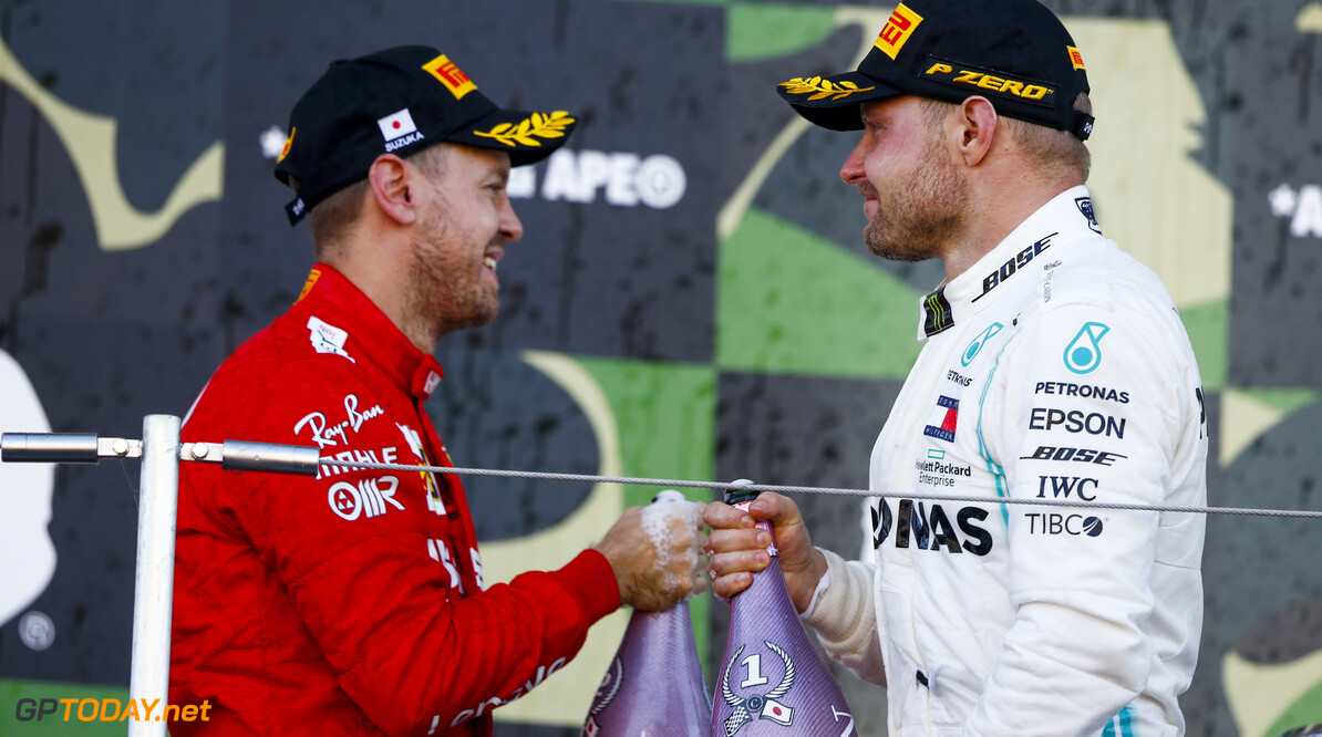 2019 Japanese GP SUZUKA, JAPAN - OCTOBER 13: Race winner Valtteri Bottas, Mercedes AMG F1 and Sebastian Vettel, Ferrari celebrate on the podium with thee champagne during the Japanese GP at Suzuka on October 13, 2019 in Suzuka, Japan. (Photo by Andy Hone / LAT Images) 2019 Japanese GP Andy Hone  Japan  Portrait ts-live